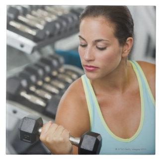 Mujer que ejercita con pesas de gimnasia azulejo cuadrado grande