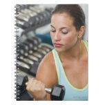 Mujer que ejercita con pesas de gimnasia cuadernos