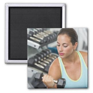Mujer que ejercita con pesas de gimnasia imán de frigorifico