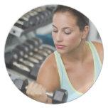 Mujer que ejercita con pesas de gimnasia platos