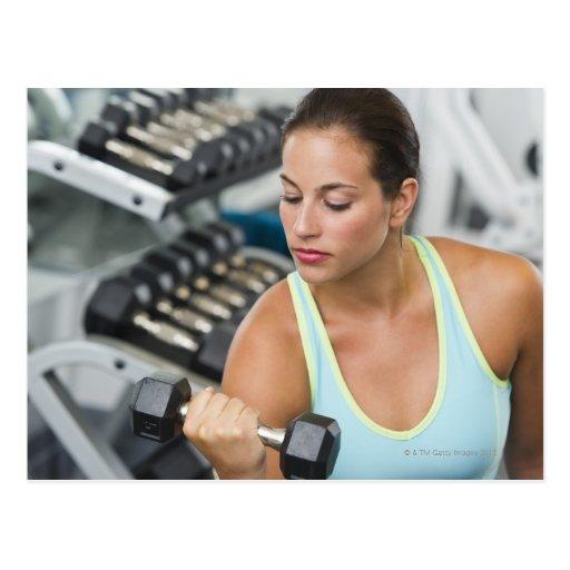 Mujer que ejercita con pesas de gimnasia postal