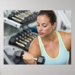 Mujer que ejercita con pesas de gimnasia poster