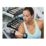Mujer que ejercita con pesas de gimnasia tarjeta postal