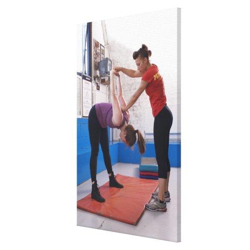 Mujer que estira con el instructor en gimnasio lienzo envuelto para galerias