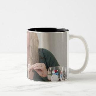 """Mujer que firma la palabra """"beso"""" en muestra ameri tazas de café"""