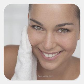 Mujer que friega su cara con el paño pegatina cuadrada