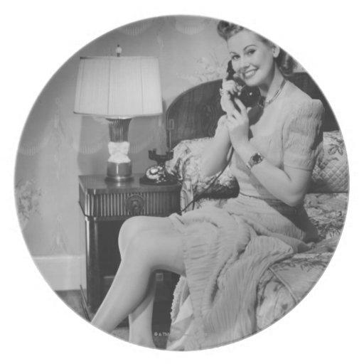 Mujer que habla en el teléfono plato de comida