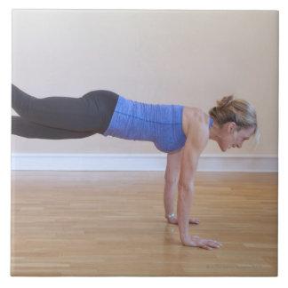 Mujer que hace actitud del ejercicio teja