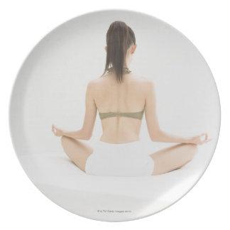 Mujer que hace yoga platos