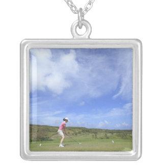 Mujer que juega a golf colgante cuadrado