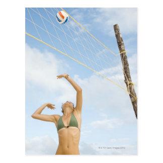Mujer que juega a voleibol al aire libre postal