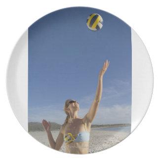 Mujer que juega a voleibol en la playa platos