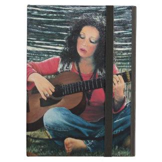 Mujer que juega música con la guitarra acústica