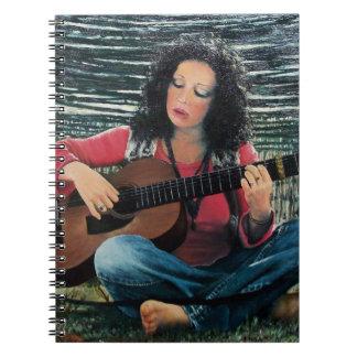 Mujer que juega música con la guitarra acústica libros de apuntes