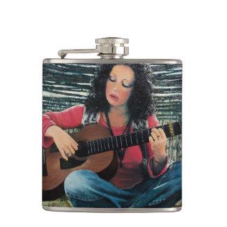 Mujer que juega música con la guitarra acústica petaca