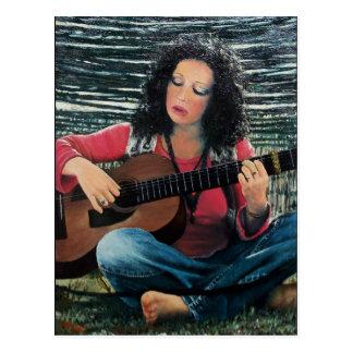 Mujer que juega música con la guitarra acústica postales