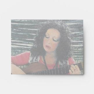 Mujer que juega música con la guitarra acústica sobre