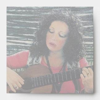 Mujer que juega música con la guitarra acústica sobres