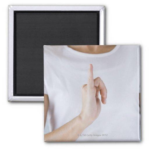 Mujer que levanta la mano con pequeño outstretched imán cuadrado