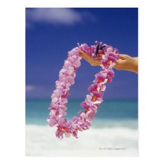 Mujer que lleva a cabo leus florales por la playa, tarjeta postal