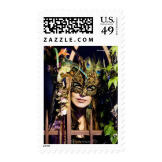 Mujer que lleva una máscara que mira hacia fuera franqueo
