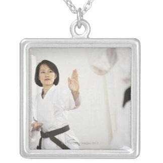 Mujer que lucha en la competencia del karate collar plateado