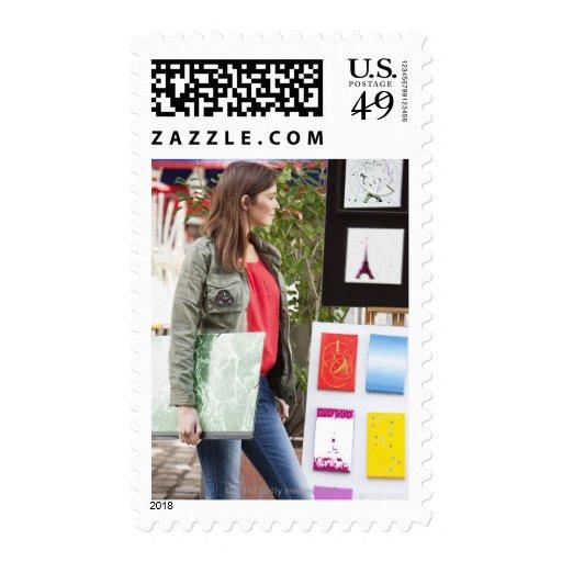 Mujer que mira las postales de la torre Eiffel a Timbres Postales