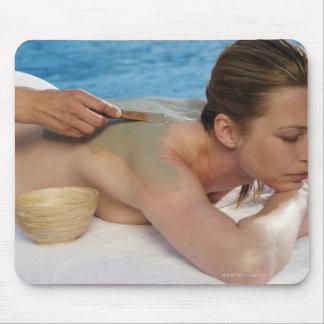 Mujer que recibe el tratamiento del balneario, tapete de raton