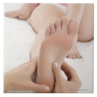 Mujer que recibe masaje del pie azulejo cuadrado grande