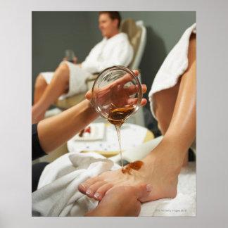 Mujer que recibe masaje del pie con aceite póster