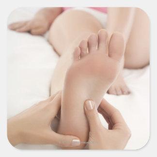 Mujer que recibe masaje del pie pegatina cuadrada