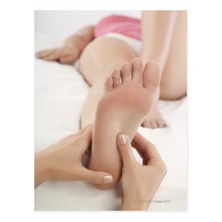 Mujer que recibe masaje del pie postal