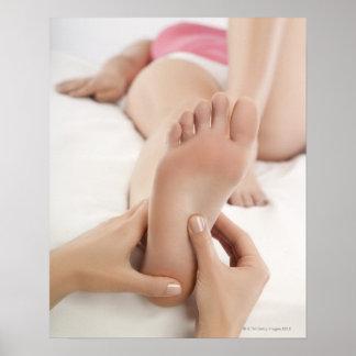 Mujer que recibe masaje del pie póster