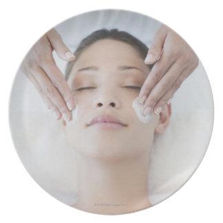 Mujer que recibe masaje facial plato para fiesta