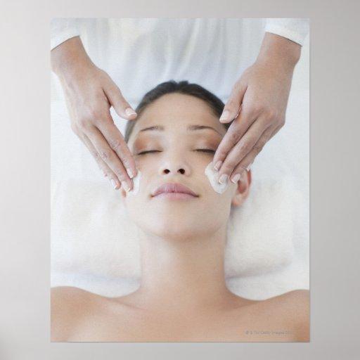 Mujer que recibe masaje facial póster