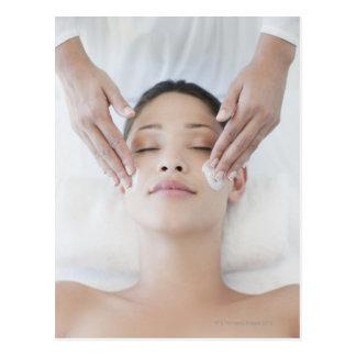 Mujer que recibe masaje facial postal