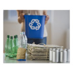 Mujer que recicla las botellas plásticas, latas y impresiones