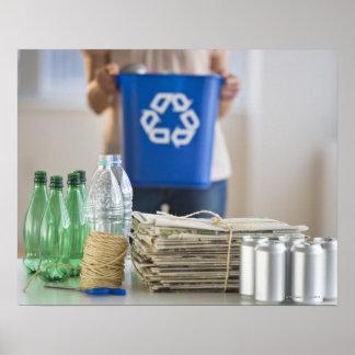 Mujer que recicla las botellas plásticas, latas y póster
