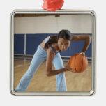 Mujer que se agacha con baloncesto, retrato adorno navideño cuadrado de metal