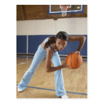 Mujer que se agacha con baloncesto, retrato postal