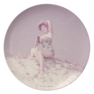 Mujer que se relaja en la playa plato de comida