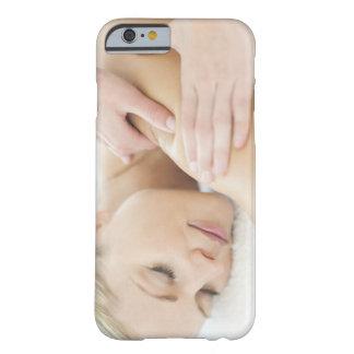 Mujer que se relaja en un balneario mientras que funda de iPhone 6 barely there