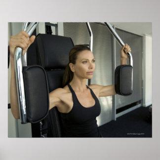 Mujer que se resuelve en un gimnasio póster