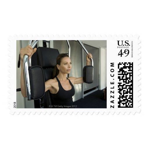 Mujer que se resuelve en un gimnasio sello