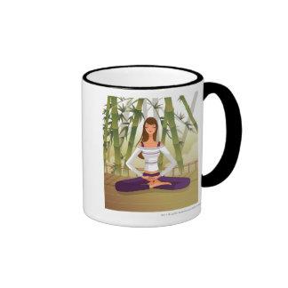 Mujer que se sienta en la posición de loto, medita taza a dos colores