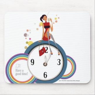 Mujer que se sienta en un reloj y que sostiene una mousepads