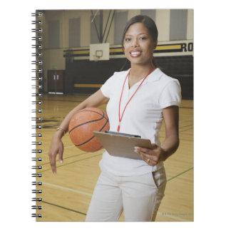 Mujer que sostiene el baloncesto y el clipbpard, libros de apuntes