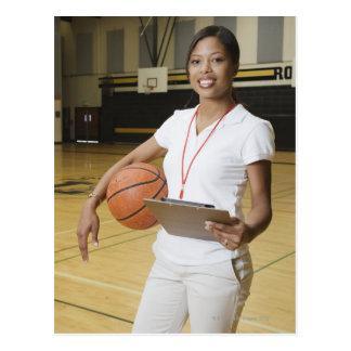 Mujer que sostiene el baloncesto y el clipbpard, postal
