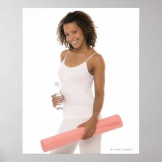 Mujer que sostiene la botella de agua y la estera  impresiones