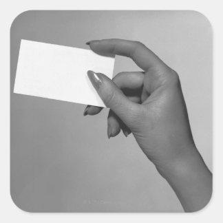 Mujer que sostiene la tarjeta calcomanía cuadradase